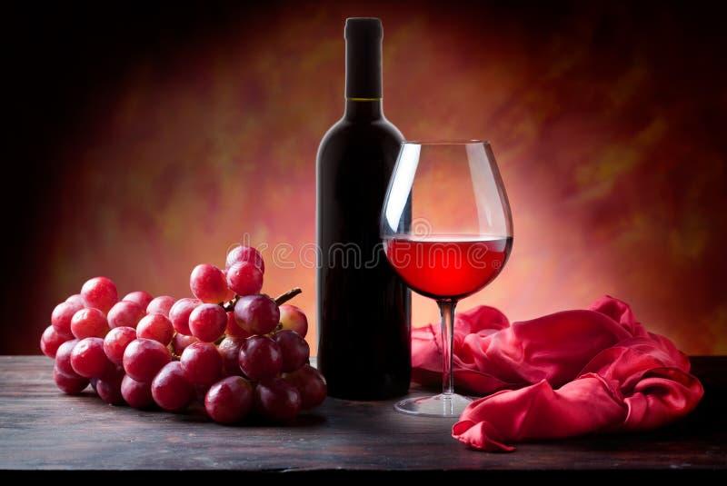 Glas des Rotweins und der Flasche mit Trauben lizenzfreies stockbild