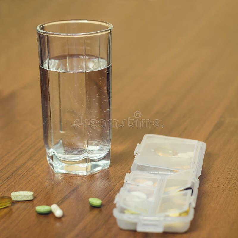 Glas des Wassers und der Mischnaturkostergänzung, Vitaminpillen im Behälter auf Holztisch lizenzfreies stockfoto