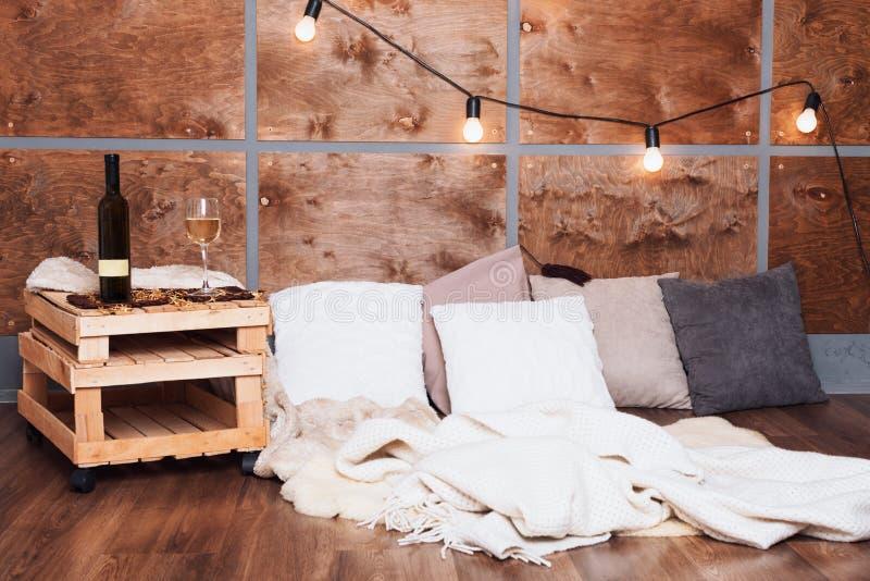 Glas des Weißweins und der Flasche im modernen Dachbodeninnenraum mit heller Girlande auf hölzerner Wand lizenzfreie stockfotografie