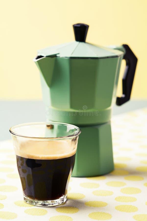 Glas do café e da cafeteira no fundo ensolarado foto de stock