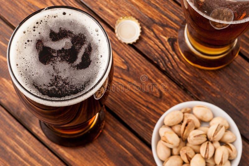 Glas dunkles kaltes schaumiges Bier, Nüsse, Flaschenkapsel, alter hölzerner Vorsprung stockfotos