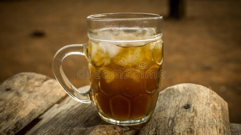 Glas Eistamarindentee asem jawa Flüssigkeit auf Holztisch lizenzfreies stockfoto