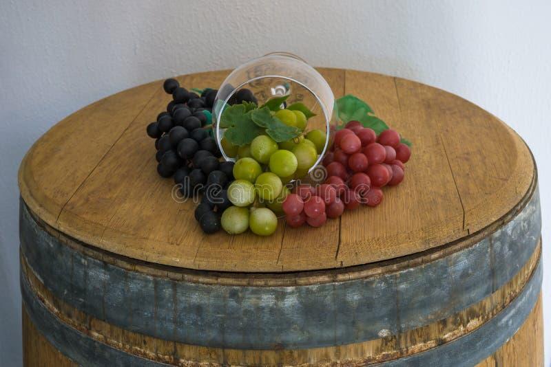 Glas en druiven en op oud eiken vat stock foto's