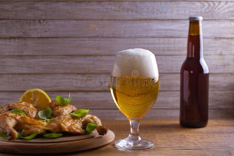 Glas en fles bier en spatchcock kip De goed-gebakken en sappige kip is goed voedsel aan glas aal stock afbeeldingen