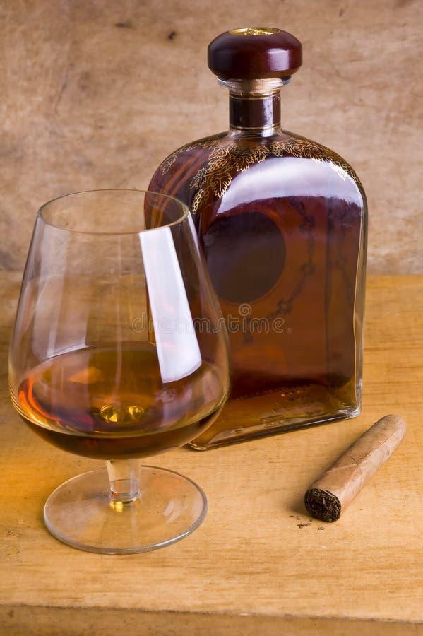 Glas en fles cognac op houten achtergrond stock fotografie