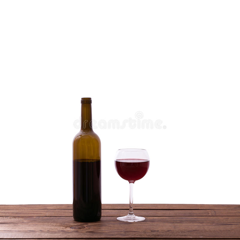 Glas en fles rode wijn op houten geïsoleerde lijst stock foto's