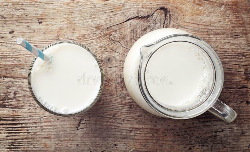 Glas en kruik melk stock foto's