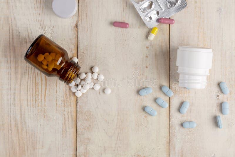 Glas en plastic flessen geneeskunde Blauwe tabletten en gekleurde medische capsules royalty-vrije stock foto's