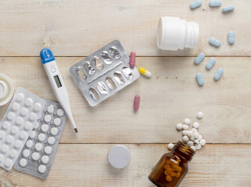 Glas en plastic flessen geneeskunde Blauwe tabletten en gekleurde medische capsules stock foto