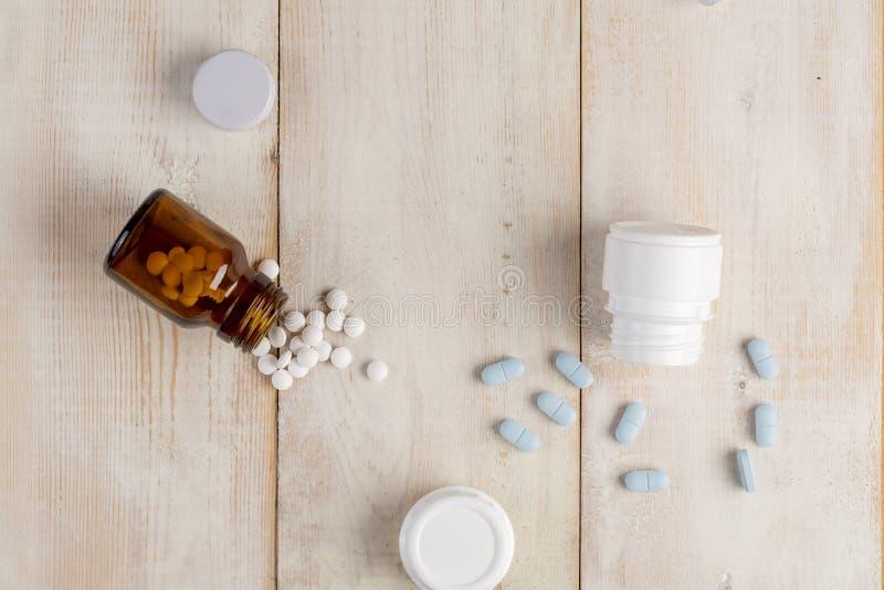 Glas en plastic flessen geneeskunde Blauwe tabletten en gekleurde medische capsules stock afbeelding