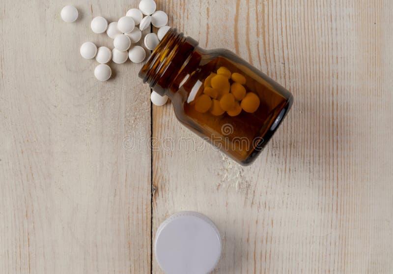 Glas en plastic flessen geneeskunde Blauwe tabletten en gekleurde medische capsules stock foto's