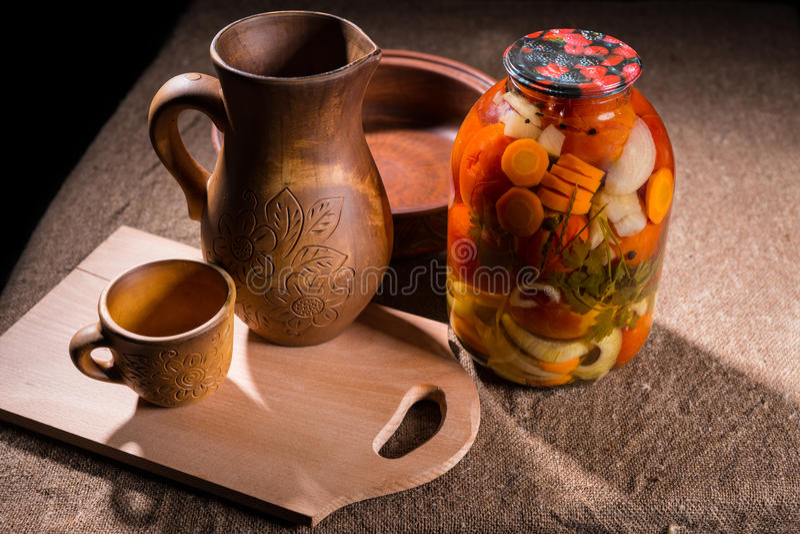 Glas Essiggurken auf Tabelle mit hölzernen Handwerkkünsten stockfoto
