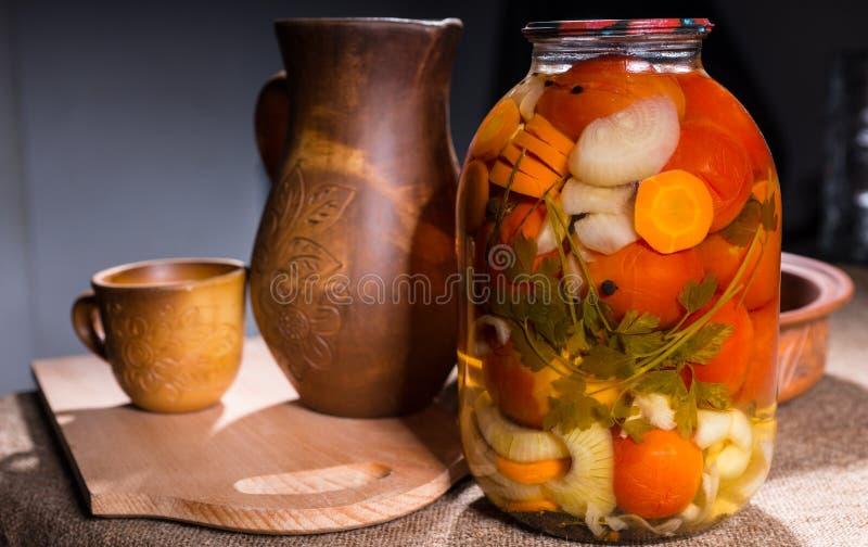 Glas Essiggurken auf Tabelle mit hölzernen Handwerkkünsten lizenzfreie stockfotos