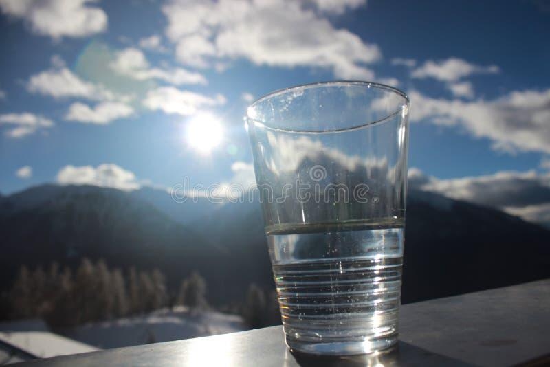 Glas est à moitié plein avec le paysage de montagne et le ciel nuageux bleu images libres de droits