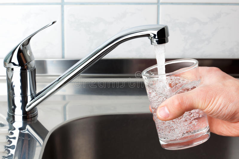 Glas füllte mit Trinkwasser vom Küchenhahn. lizenzfreie stockfotografie