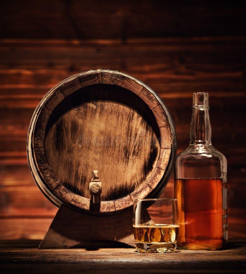 Glas, fles en vaatje whisky met ijsblokjes op hout worden gediend dat stock afbeeldingen