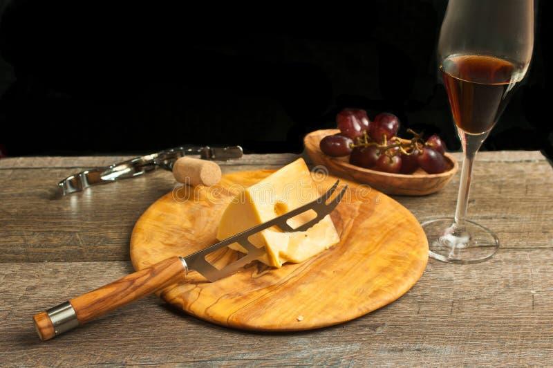Glas Franse wijn en wig van kaas met kom van rode druiven stock afbeeldingen