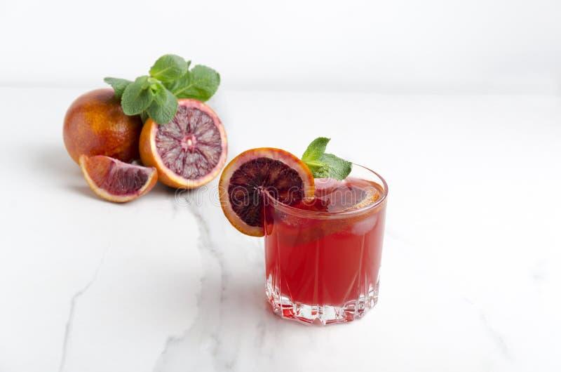 Glas frischen gemachten Blutorange Margarita mit Scheiben der Blutorange, der Eiswürfel und der Minze auf der weißen Marmortabell stockfotos