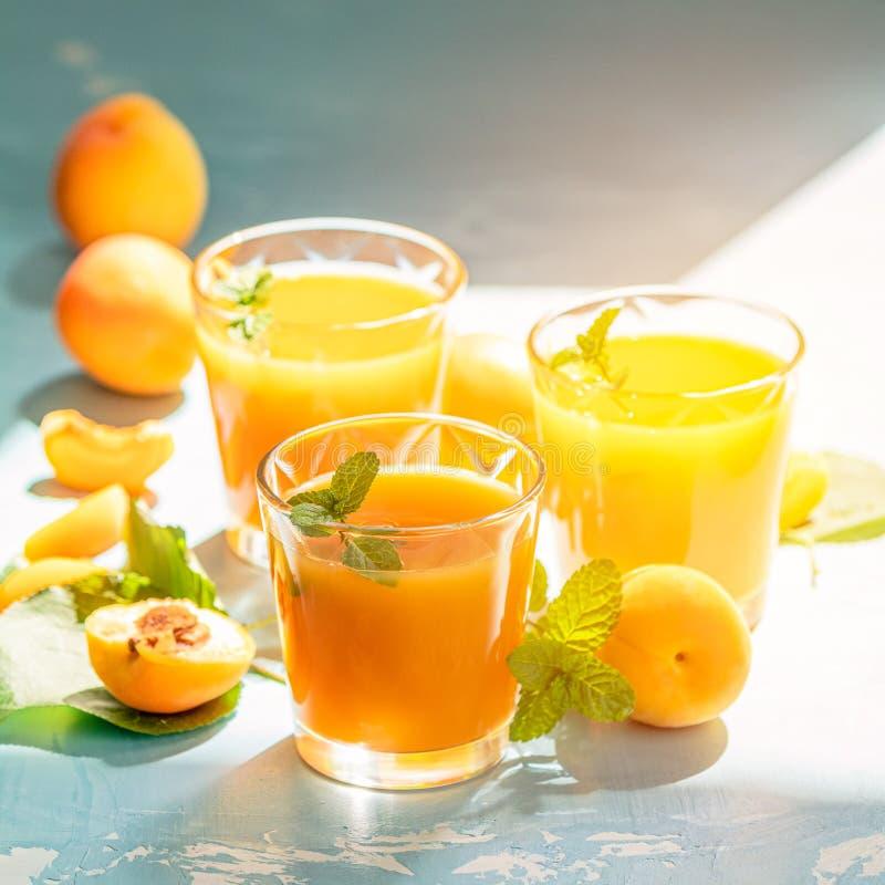 Glas frischer gesunder Aprikosensaft im sonnigen Licht stockfotografie