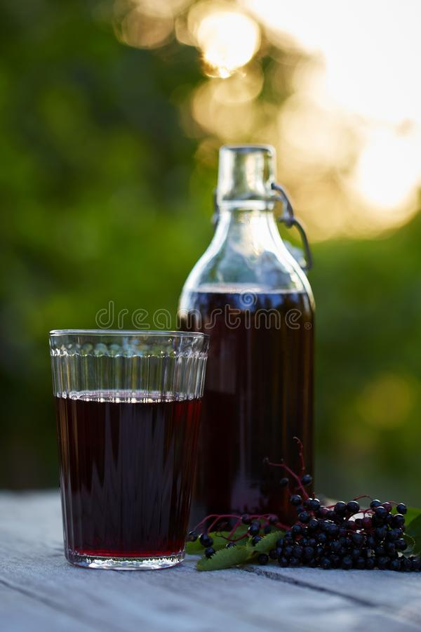 Glas frischer Holunderbeersirup und -holunderbeeren lizenzfreies stockfoto