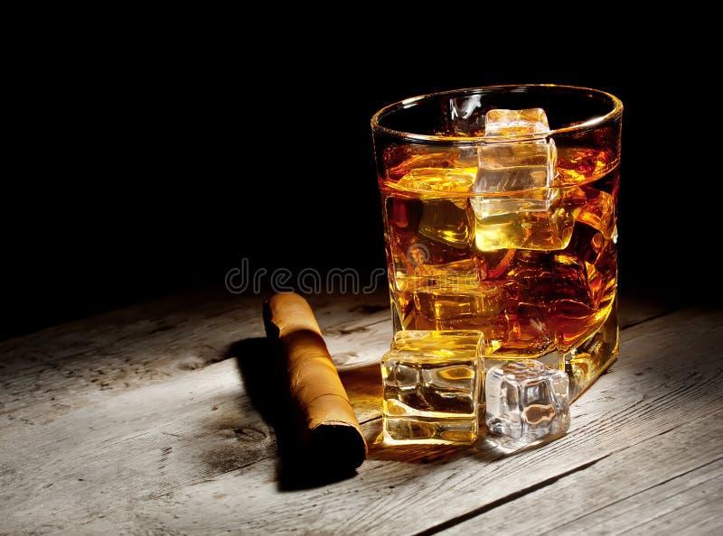 Glas gealterter Whisky mit Zigarren- und Eiswürfeln lizenzfreie stockfotos