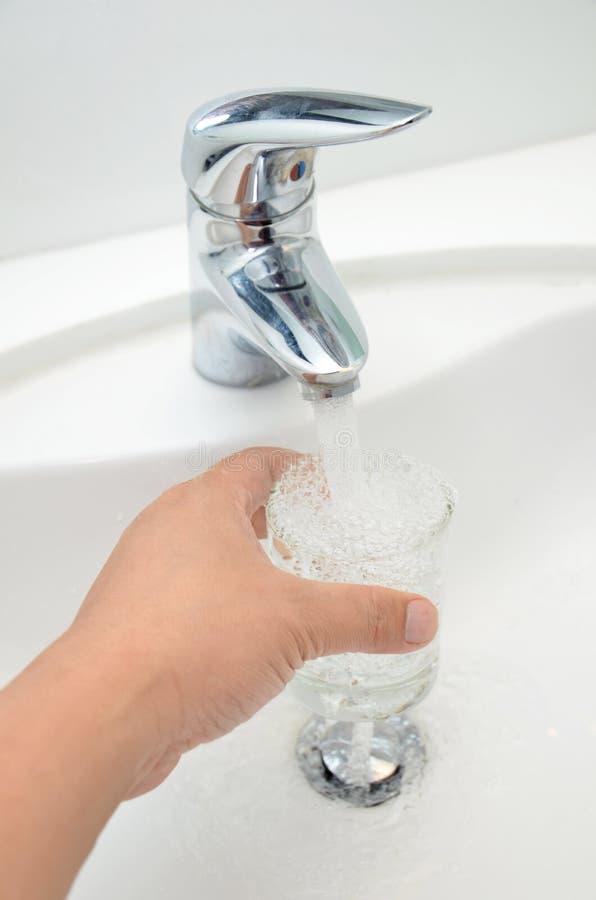 Glas gefüllt mit Trinkwasser vom Hahn lizenzfreie stockfotografie