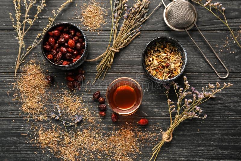 Glas heißer Tee mit Trockenblumen und Hagebutten auf Holztisch stockfotos