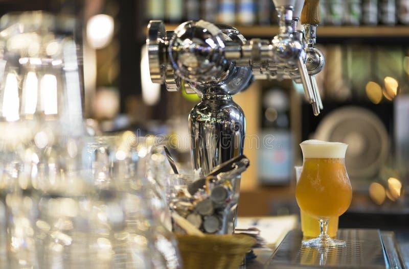 Glas helles Bier, dienendes frisches Bier im Barzähler stockfotografie