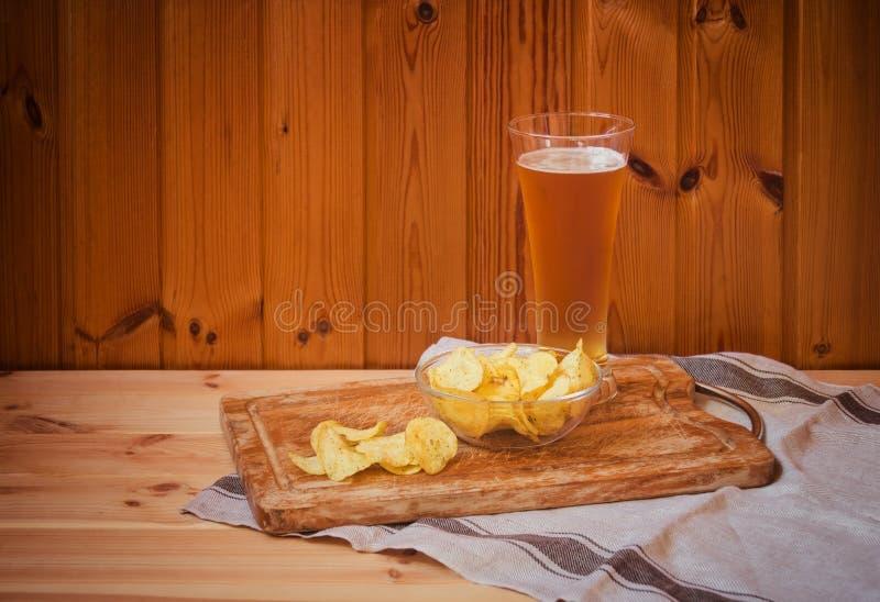 Glas helles Bier mit Kartoffelchips auf Holztisch lizenzfreie stockbilder