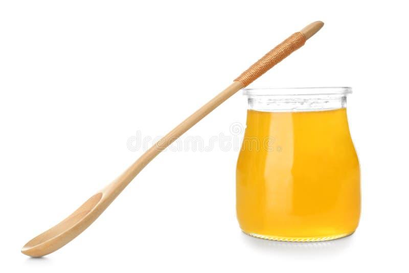 Glas Honig mit h?lzernem L?ffel auf wei?em Hintergrund lizenzfreies stockbild