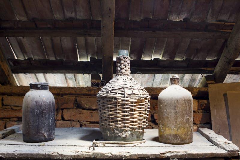 Glas, houten en metaalvoorwerpen in de zolder met stof en spiderwebs royalty-vrije stock afbeelding