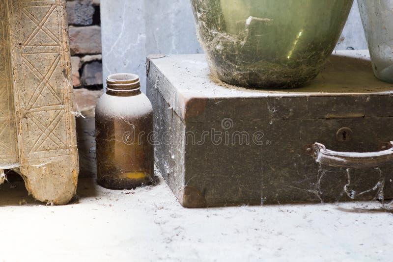 Glas, houten en metaalvoorwerpen in de zolder met stof en spiderwebs royalty-vrije stock fotografie