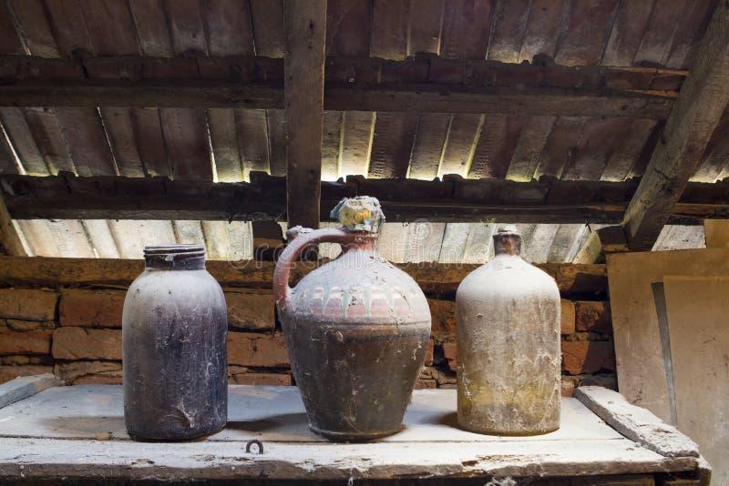 Glas, houten en metaalvoorwerpen in de zolder met stof en spiderwebs stock foto's
