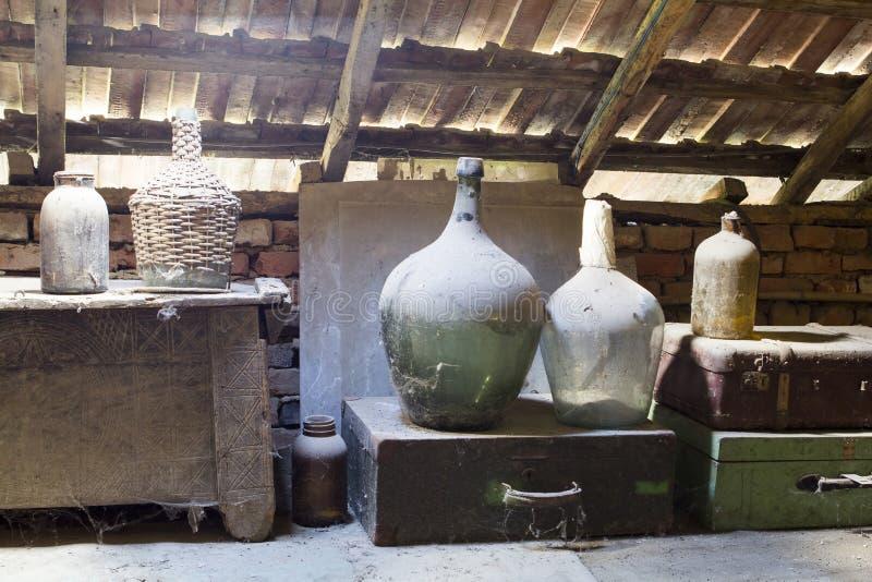 Glas, houten en metaalvoorwerpen in de zolder met stof en spiderwebs royalty-vrije stock afbeeldingen