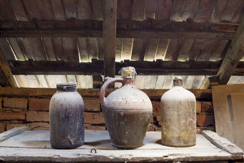 Glas, houten en metaalvoorwerpen in de zolder met stof en spiderwebs stock foto
