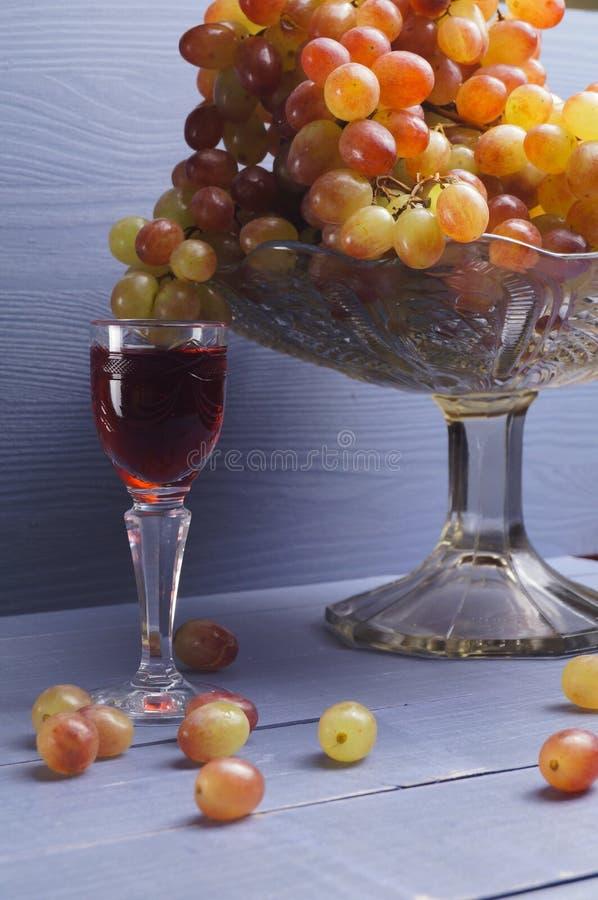 Glas jonge wijn met druiven stock fotografie