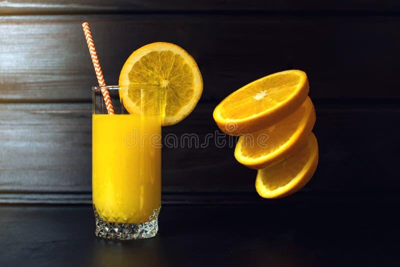 Glas jus d'orange met het gesneden oranje hangen in lucht stock foto