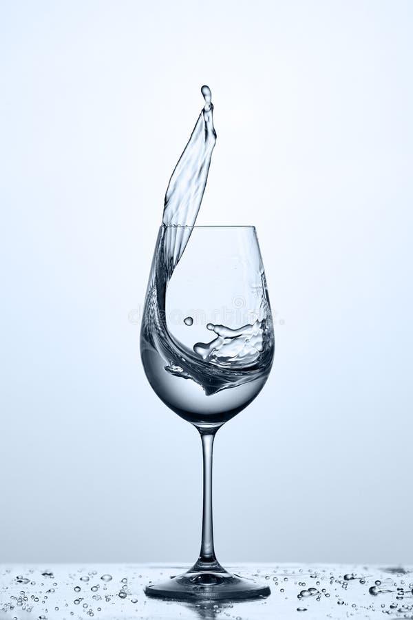 Glas kühles saubereres Spritzwasser, während die Stellung auf dem Glas mit Wasser gegen hellen Hintergrund sprudelt stockfotografie
