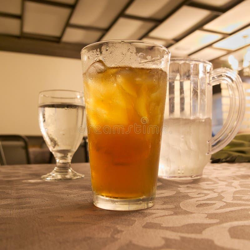 Glas kaltes Eistee mit Eis und Becher und Pitcher Wasser stockfotografie