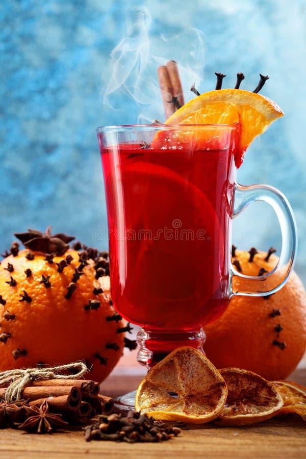 Glas Kerstmis hete overwogen wijn op houten lijst met species en sinaasappelen tegen bevroren venster close-up stock fotografie