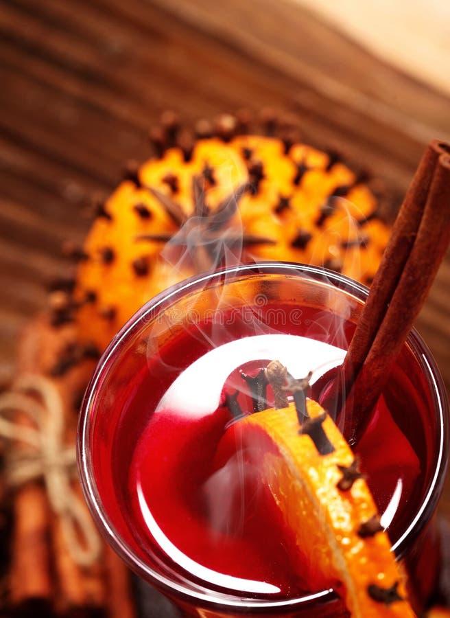 Glas Kerstmis hete overwogen wijn op houten lijst met species en sinaasappelen tegen bevroren venster close-up Hoogste mening stock foto