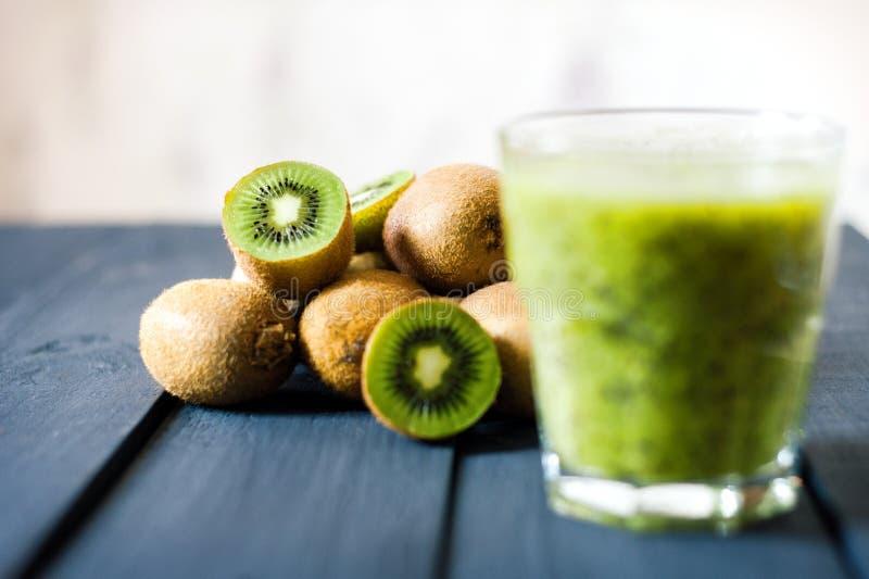 Glas Kiwisaft mit frischen Früchten auf Holztisch lizenzfreies stockfoto