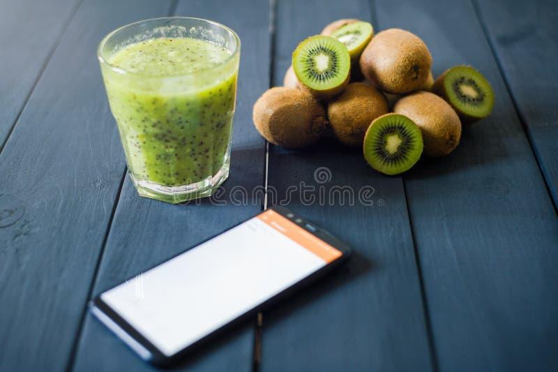 Glas Kiwisaft mit frischen Früchten auf Holztisch lizenzfreie stockfotos