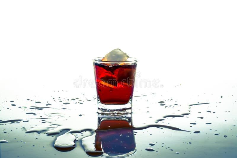 Glas Knallsoda mit Eiswürfel mit Sprayspritzen auf dem Tisch und lokalisiert lizenzfreie stockfotos