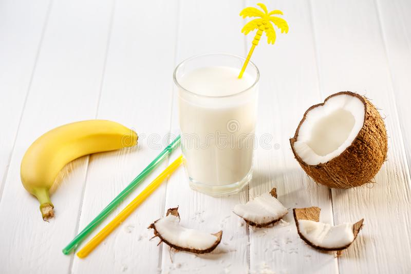 Glas kokosmelk op witte houten lijst, bananen tropisch Selectieve nadruk stock afbeeldingen