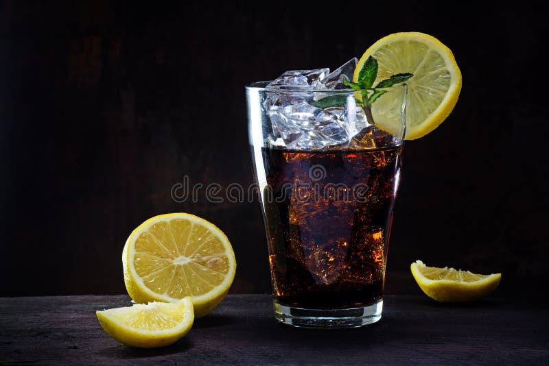 Glas kola of ijsthee met citroenplakken en pepermuntgarnis stock fotografie