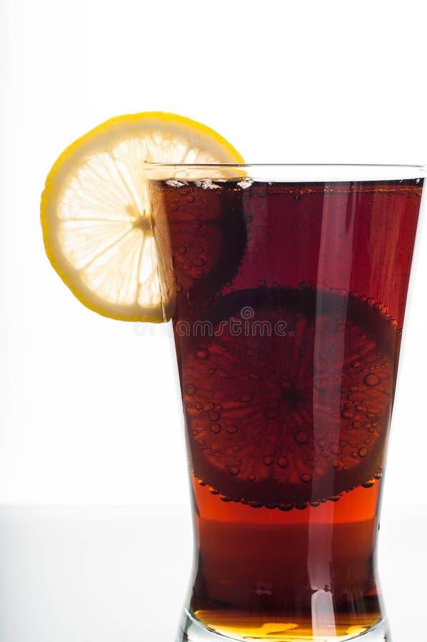 Glas Kolabaum mit geschnittener Zitrone stockbilder