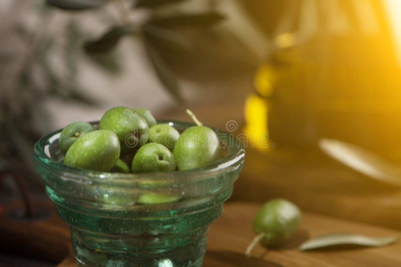 Glas kopp av oliv med extra jungfrulig olivolja i glasflaska på lantlig bakgrund close upp arkivfoton