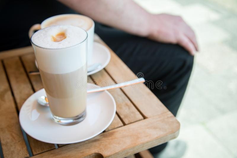 Glas of Latte Macchiato and cup of Cappuccino coffee with milk on wooden table outside of street caf royalty free stock images