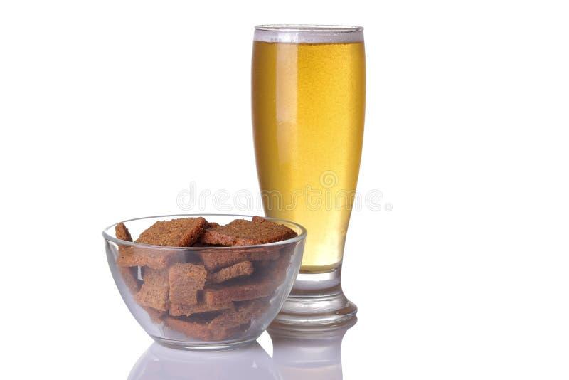 Glas licht bier met gezouten broodkruimels op wit geïsoleerde achtergrond stock afbeeldingen